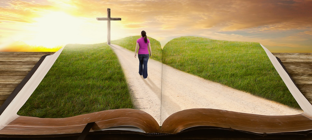 A woman walks along a road on a book towards the cross.